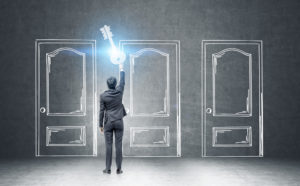 Rear view of a businessman in a dark suit holding a giant key standing near a black wall with three doors drawn with chalk. Concept of an opportunity. Toned image