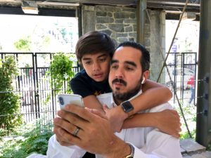 manuel suarez with son using white iphone